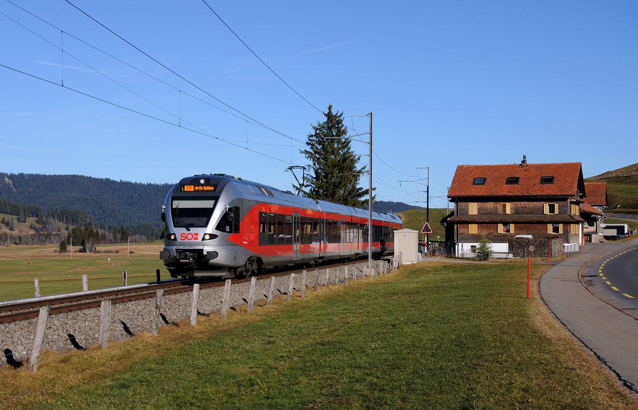 Kurz vor dem Ort Rothenthurm führt die Strecke der Südostbahn an der Kantonsstraße 4 entlang. Ein Flirt-Triebzug rollt gerade als S31 nach Arth-Goldau an einem alten mit Holztafeln verkleideten haus vorbei.