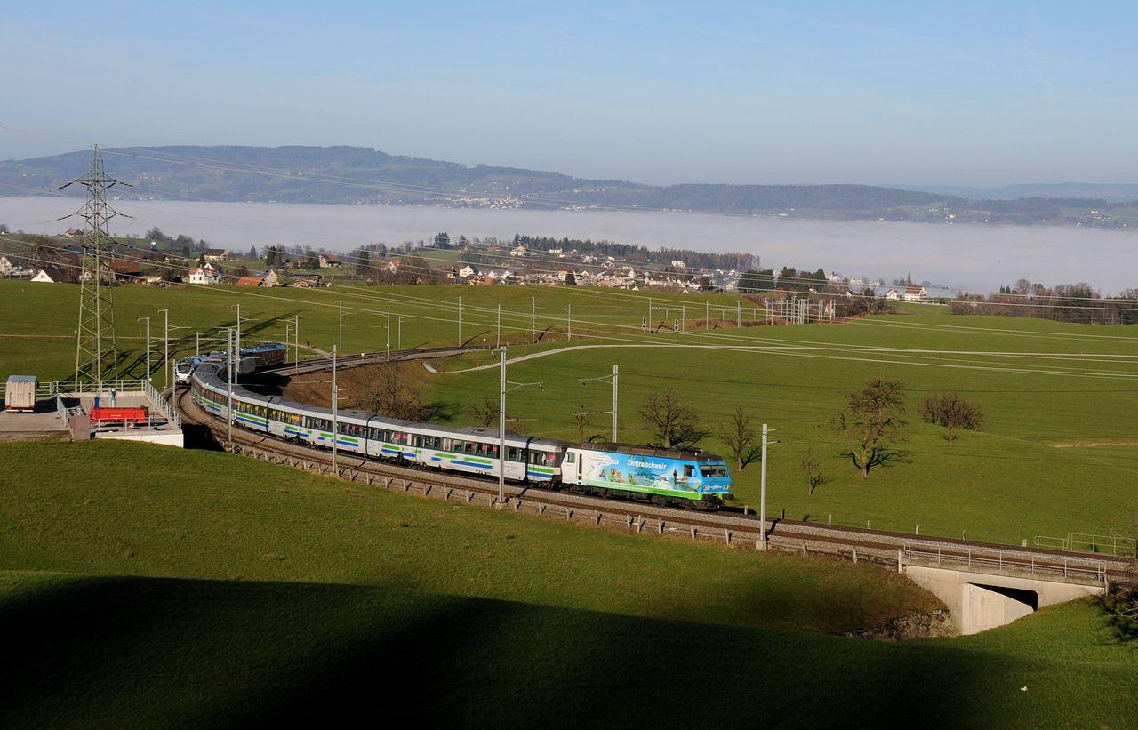 Überwiegend werden aber die Loks der Reihe Re456 und die ehemaligen NPZ Triebzüge vor den Voralpen-Expressen eingesetzt. Hier ist bei Samstagern eine Garnitur nach Luzern bergwärts unterwegs. Man blickt auf den Zürichsee welcher unter einem Nebelmeer liegt.