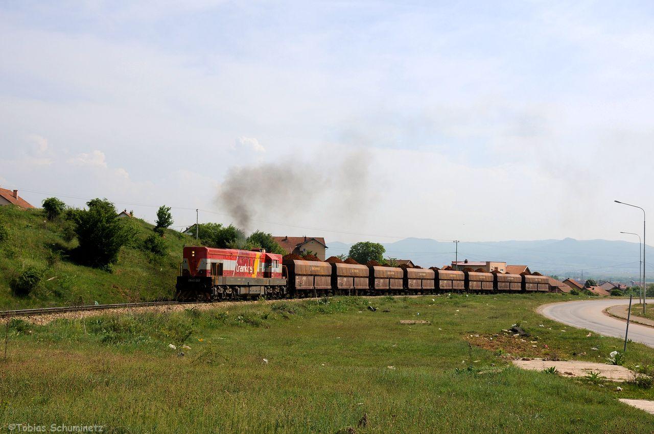 Das lange Anschlussgleis zu NewCo-Ferronikeli hat eine starke Steigung, weshalb Lok 003 den Zug in zwei Teilen vom Bahnhof in das Werk fahren muss. Hier kurz vor dem Werkstor. Das Werk ist übrigens ähnlich wie ein Hochsicherheitstrakt geschützt.
