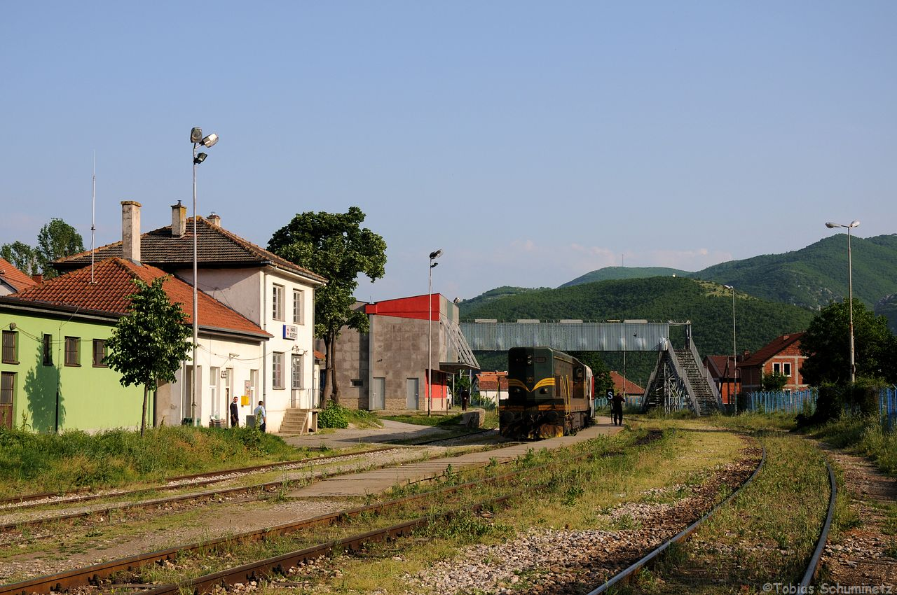 Wir liefen zurück um die mazedonische Lok mit dem Bahnhofsgebäude von Hani i Elezit aufnehmen zu können. Das Bild vorher wurde von dem Fußgängersteg im Hintergrund aus gemacht. Die Halle mit dem Roten Dach ist ein Lager- und Zollschuppen.