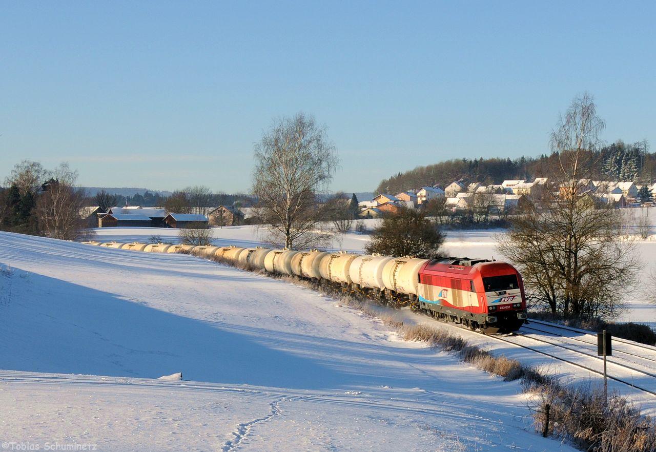 Beginnen möchte ich am Vormittag des 6. Januars. Das Wetter war gut und es wurde mir ein Kesselwagenzug Richtung Norden gemeldet. Daher fuhr ich schnell nach Escheldorf zwischen Reuth und Wiesau. Ich hatte noch ein paar Minuten ehe sich die 223 031 der EVB mit einem Zug, vollbeladen mit staatlichen Spritreserven von Tschechien die Steigung hinaufkämpfte.