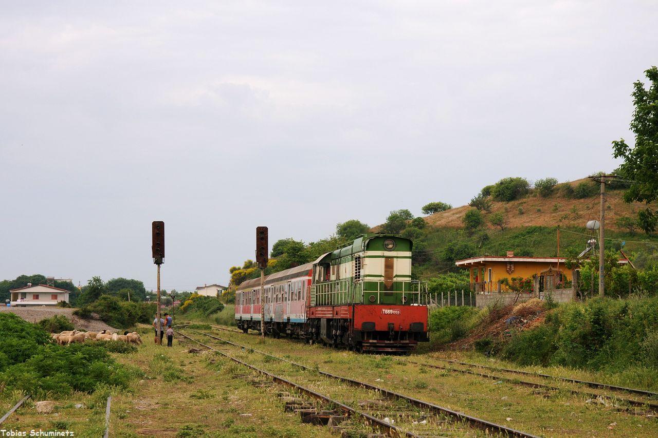 Im Bahnhof von Bishquem war leider gerade keine Sonne als der Zug die in den Gleisanlagen grasende Schafherde samt Hirten passiert. Kurz vor dem Zug wurden sie zur Seite getrieben.